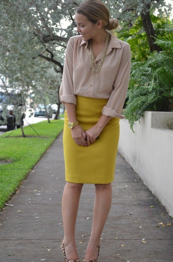 yellow skirt polka dotted grey sweater is tucked in bright yellow flared skirt completed  with black HXTLVIM